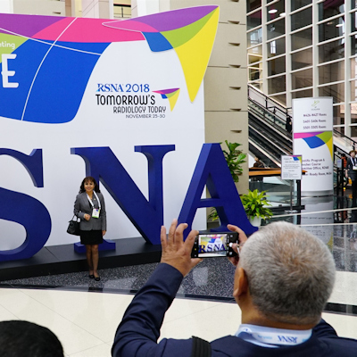 Attendees taking photos with the RSNA logo
